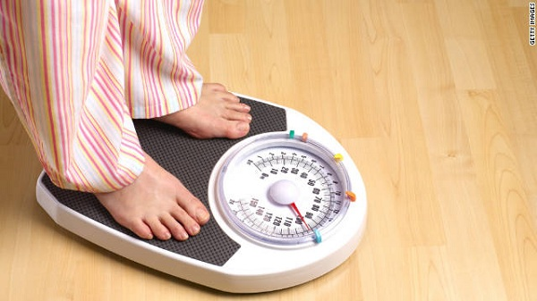 Person weighing themselves on scale
